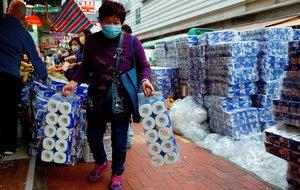 Una mujer compra papel higiénico protegida con mascarilla por temor al coronavirus en un mercado de Hong Kong.