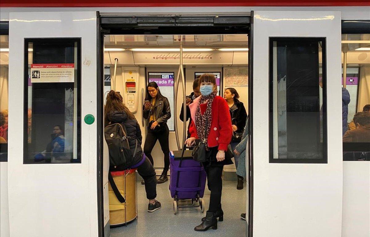 Una mujer con mascarilla para protegerse del coronavirus, en el metro de Barcelona.