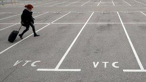 Una mujer pasa por los estacionamientos vacíos asignados para los VTC en el aeropuerto del Prat.