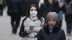 Una mujer pasea por Moscú con una mascarilla como protección.