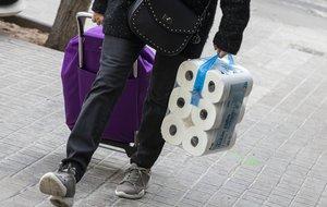 Una mujer arrastra el carro de su compra con rollos de papel higiénico.
