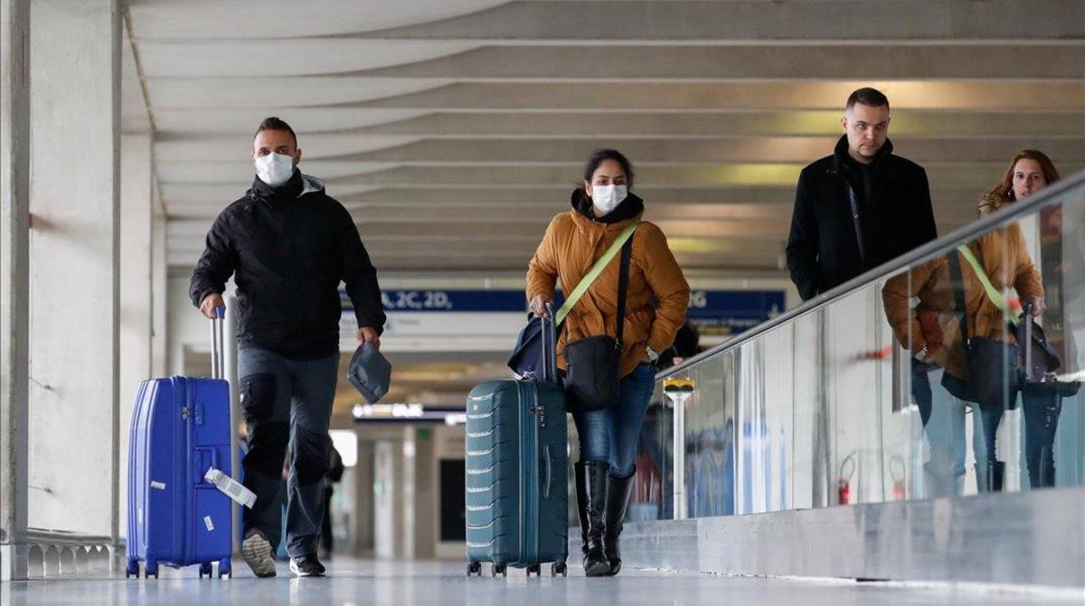 Una pareja con mascarillas en el aeropuerto Charles de Gaulle.