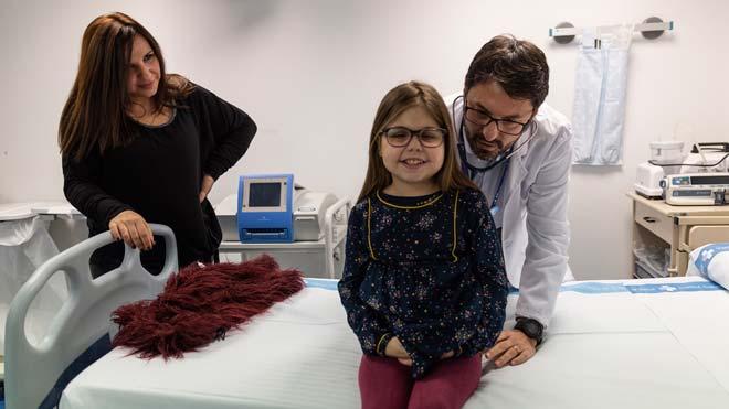 Vall d'Hebron realiza un triple trasplante a una niña por primera vez en España. En la foto, Iria con su madre y uno de sus médicos.
