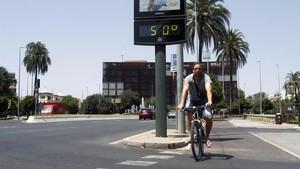 Un joven pasa con su bicicleta junto a un termómetro, expuesto al sol,que marca 50 grados en Córdoba.
