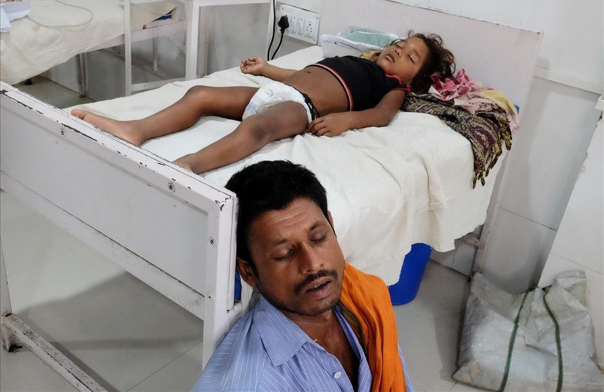 Un hombre duerme junto a su hija que sufre de síndrome de encefalitis aguda en un hospital de Muzaffarpur, en el estado oriental de Bihar, India.
