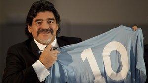 Maradona sostiene una camiseta del Nápoles, con su legendario número 10.