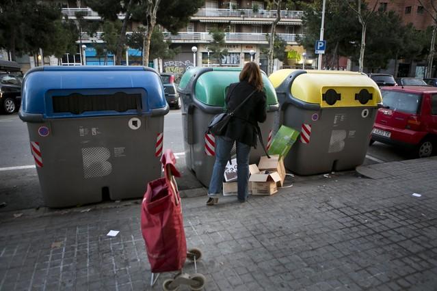 Una dona diposita residus en contenidors aBarcelona.