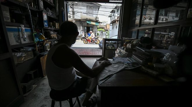 Un comerciante ve como pasea Marc Márquez con su Honda por Bangkok