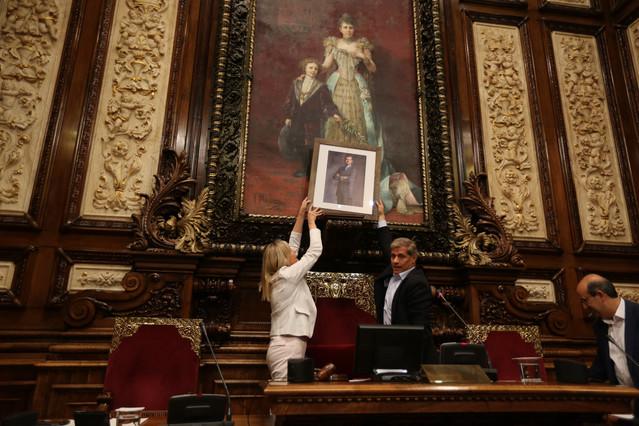 Alberto Fernández Díaz sostiene una foto del rey Felipe en el lugar donde estaba el busto del rey Juan Carlos, este viernes en el Ayuntamiento de Barcelona.