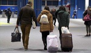 Algunos asistentes a la Cumbre del Clima de Madrid salen del recinto con sus maletas.