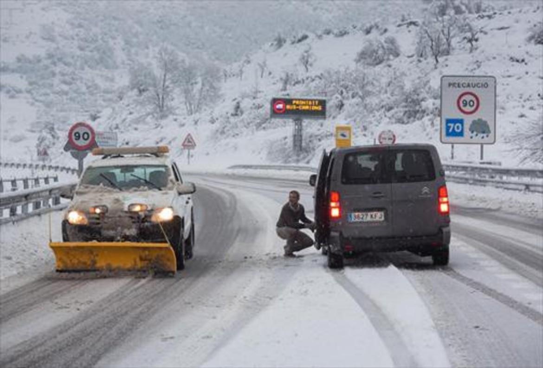 Un conductor pone cadenas a su vehículo en la C-16, dirección al túnel del Cadí.