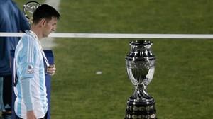 El delantero argentinoLeo Messi mira cabizbajo la Copa América tras perder la final ante Chile en los penaltis