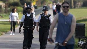 Dos policías patrullan por un parque de Londres este sábado mientras hay gente paseando o haciendo deporte.