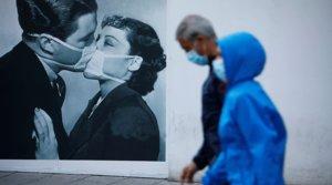 Dos transeúntes pasan junto al cartel de un beso entre dos personas con mascarilla, el domingo 10 de mayo.