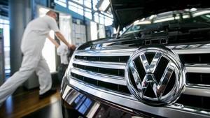 Un empleado de la Volkswagen de Dresde, junto a un Passat.