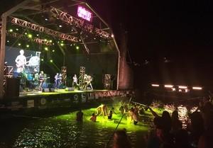 El escenario del festival Pirineos Sur, con el grupo Chico Trujillo, y espectadores en el agua.