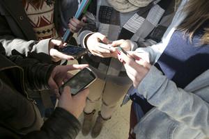 Un grupo de menores, con sus teléfonos móviles en Barcelona.