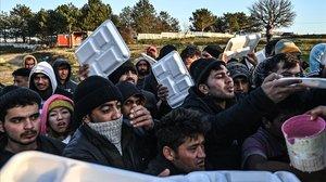 Un grupo de migrantes esperan que les sirvan comida en teritorio turco mientras esperan cruzar el río Meritsa para entrar en Grecia.