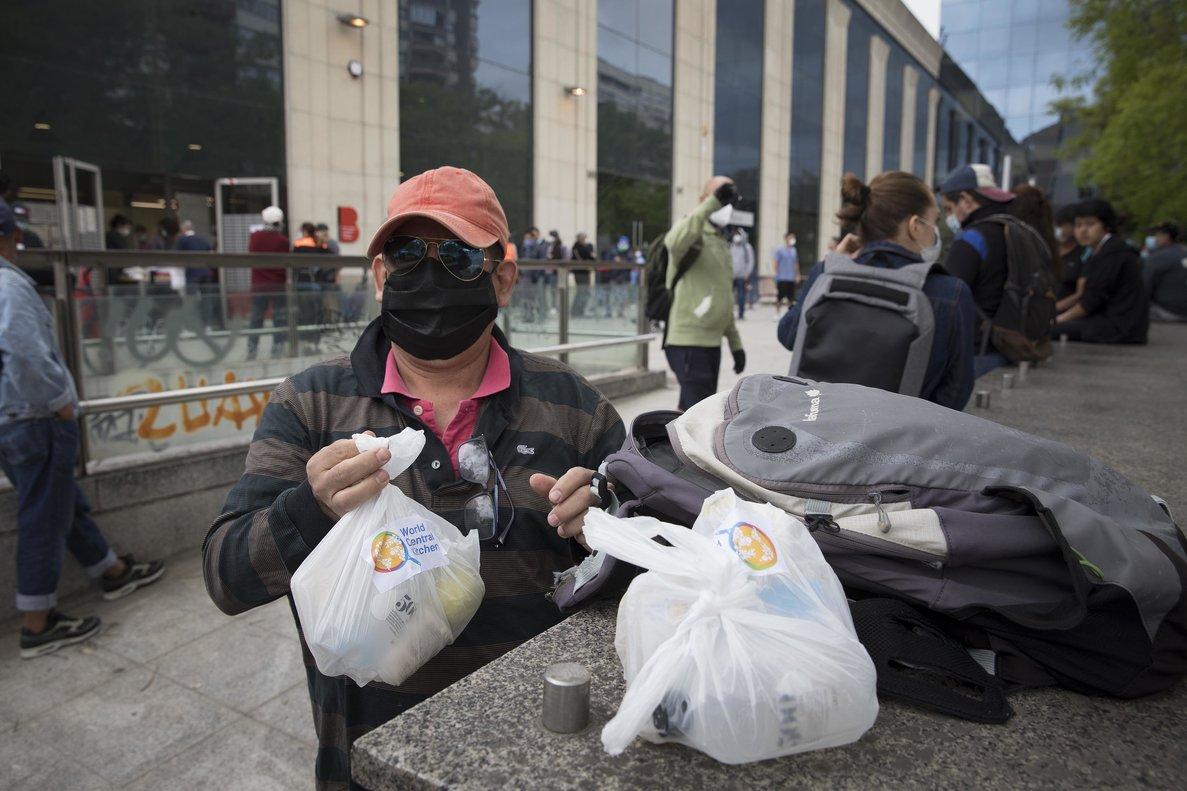 Un hombre recoge bolsas de comida que distribuye el Banc dels Aliments.