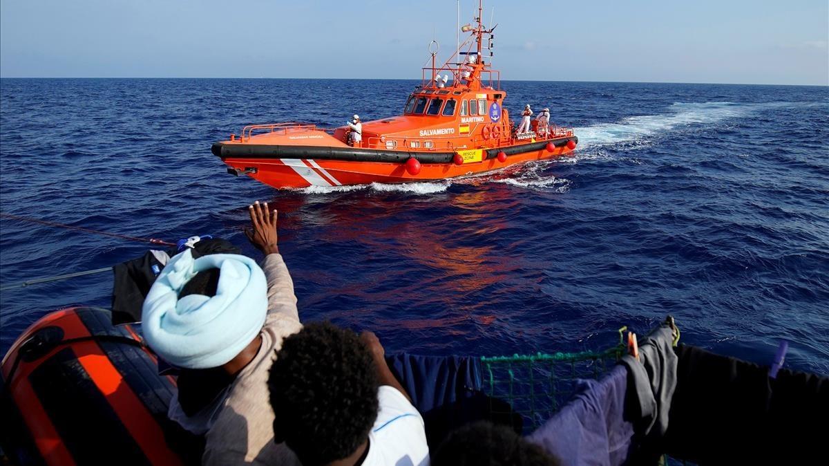 Inmigrantes hacen señas al barco de rescate de la oenegé Proactiva Open Arms, en el Mediterráneo, en una imagen de archivo.