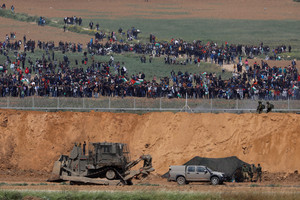 Israeli soldiers patrol next to the border fence on the Israeli side of the Israel-Gaza Strip border, as Palestinians protest on the Gaza side of the border, March 30, 2018. REUTERS/Amir Cohen