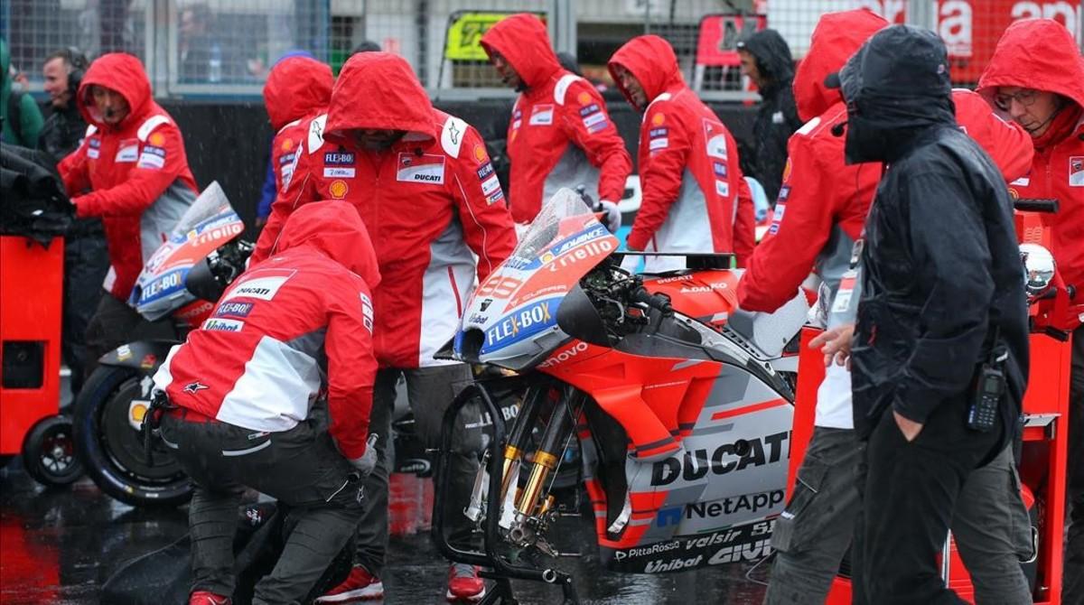 Los mecánicos de Ducati retiran la moto de Jorge Lorenzo de la parrilla, inundada, de Silverstone.