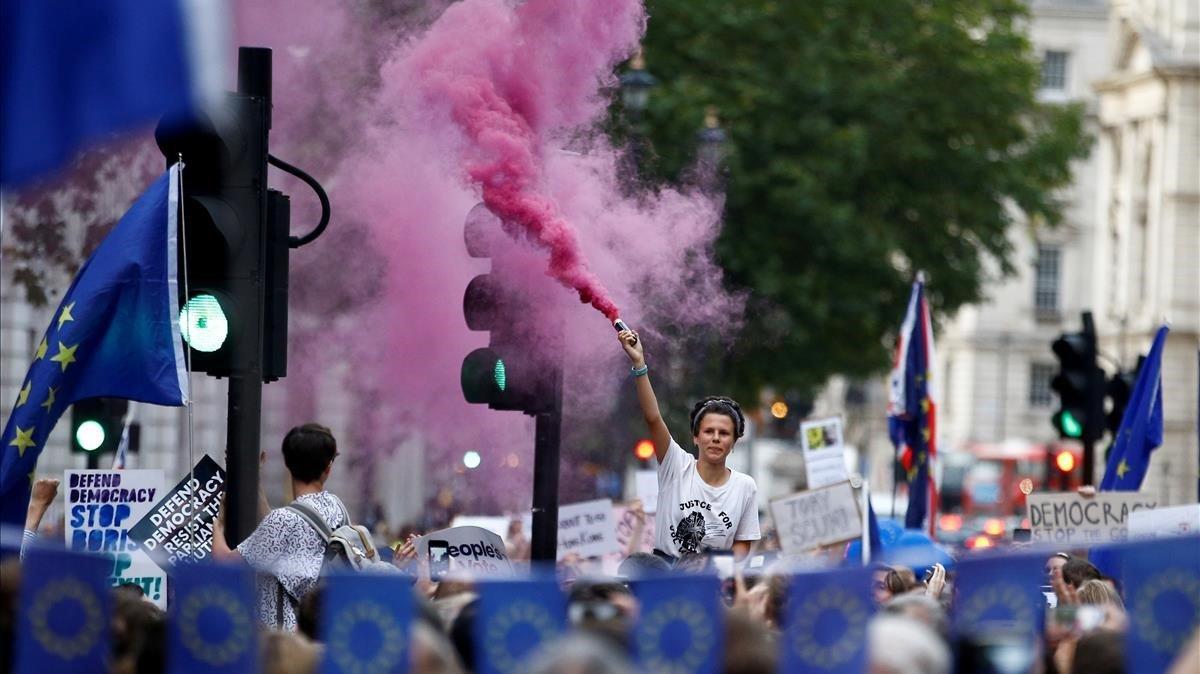 Un manifestante anti-Brexit libera humo de color afuera de las Casas del Parlamento en Londres.