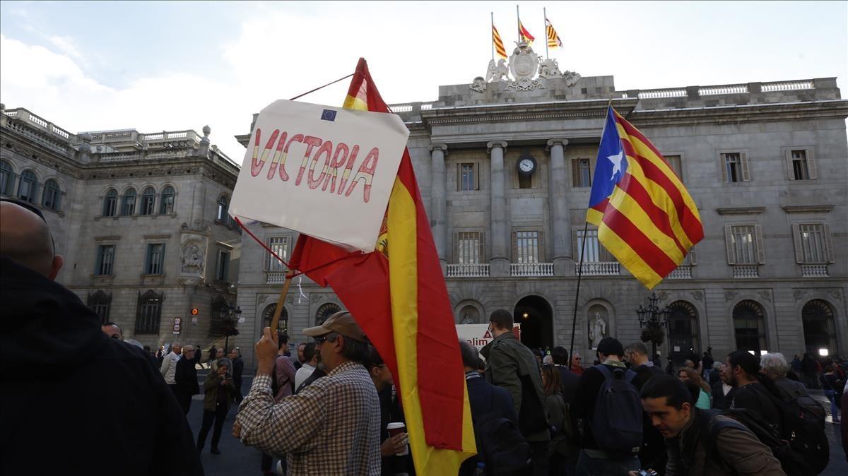 Un manifestante con una estelada y otro con una bandera española en la plaza de Sant Jaume.