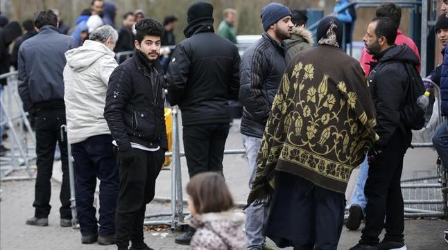 Migrantes esperan para registrarse frente a la oficina federal de migración y refugiados del distrito de Spandau, en Berlín (Alemania).