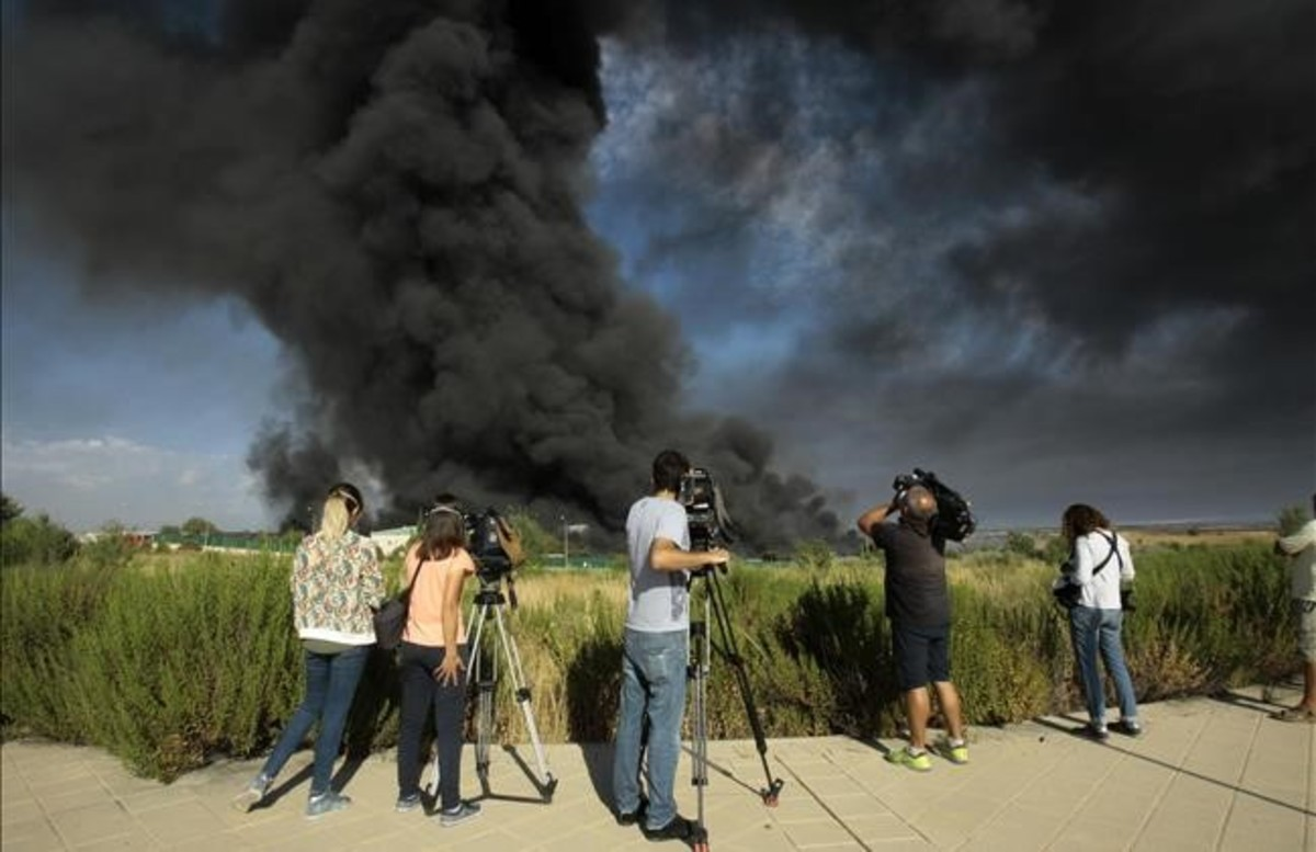 Unos periodistas toman imágenes de la gran columna de humo producida este viernes en un polígono deChiloeches, Guadalajara.