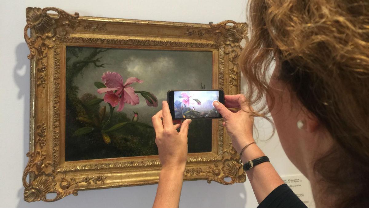 Una visitante fotografía 'Orquídea y colibrí cerca de una cascada' deMartin Johnson Heade, la obra de la exposición preferida de Carmen Thyssen.