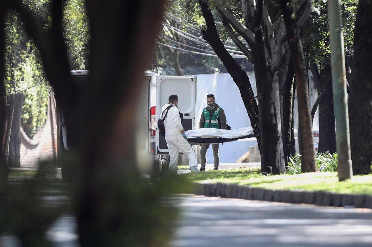 Peritos forenses se llevan a una de las víctimas.