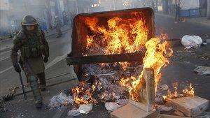 Un policía pasa junto a un contenedor ardiendo en Viña del Mar.