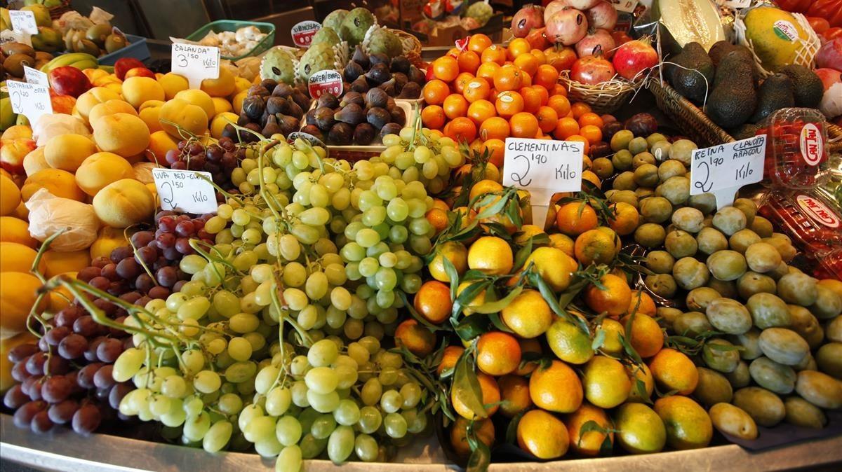 Puesto de fruta en el mercado de Fort Pienc, con productos de otoño comouvas, higos y mandarinas.