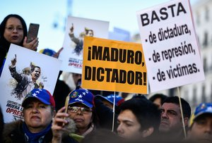 People hold placards readingMadurodictatorandEnough of dictatorshiprepresion and victimsduring a demonstration called by Venezuelan citizens against President Nicolas Maduroin Madrid-Photo by OSCAR DEL POZOAFP