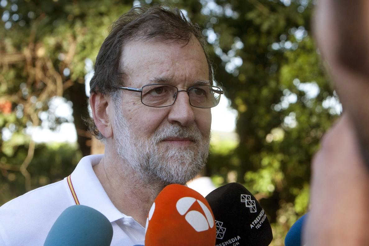 El presidente del Gobierno Mariano Rajoy atiende a los medios de comunicacion durante su paseo por las orillas del rio Umia a su paso por la localidad de Ponte Arnelas en Ribadumia Pontevedra en el inicio de sus vacaciones.