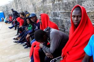 Algunos de las personas de origen subsahariano rescatadas por Salvamento y atendidas por Cruz Roja esperan en el puerto de Tarifa su traslado por la Guardia Civil.