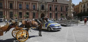 Un coche de caballos y una patrulla policial junto a una de las tribunas, en la Plaza de la Virgen de los Reyes, que estaban preparadas para la visita del presidente de EEUU Barack Obama a Sevilla, que finalmente ha sido cancelada