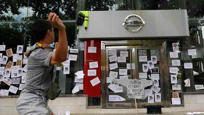 Trabajadores de Nissan empapelan un concesionario de la marca en L'Hospitalet. En la foto, un trabajador lanza un huevo contra una tienda en Barcelona.