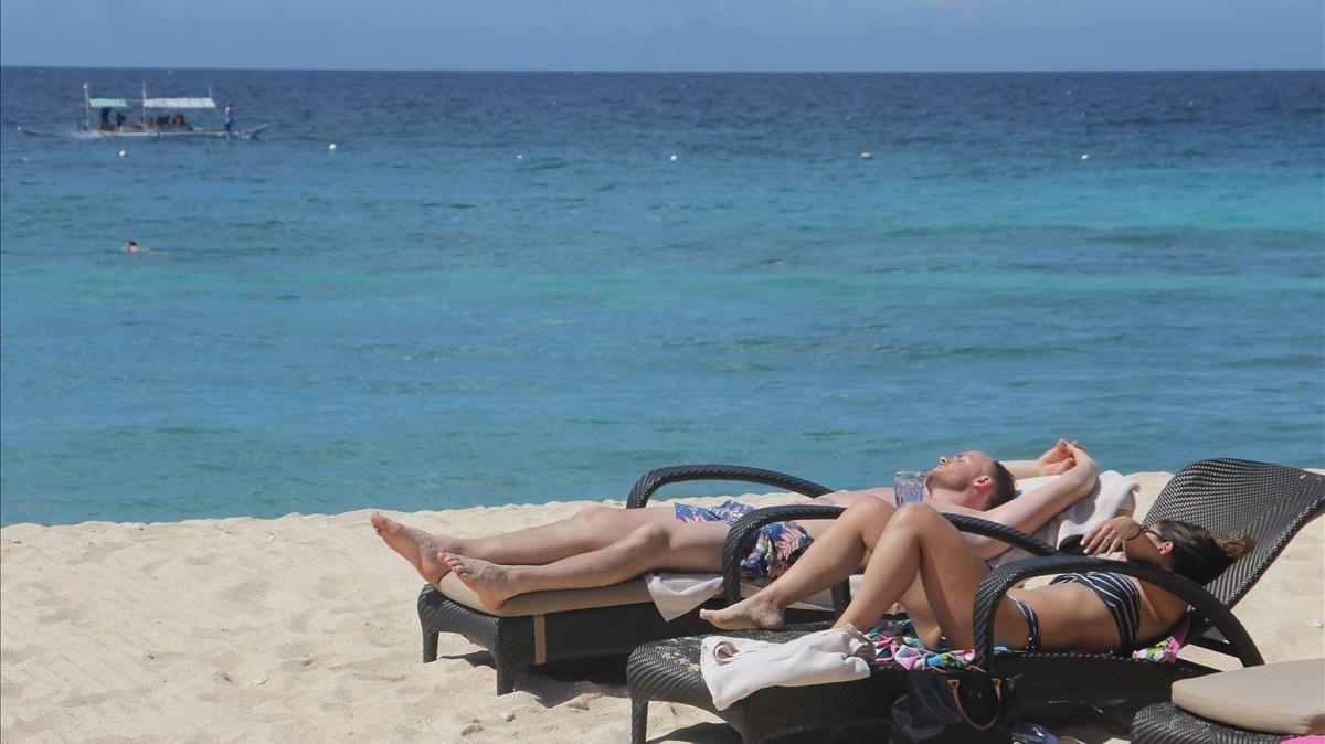 Una pareja de turistas toman el sol en una de las playas de Boracay, en enero del 2018.