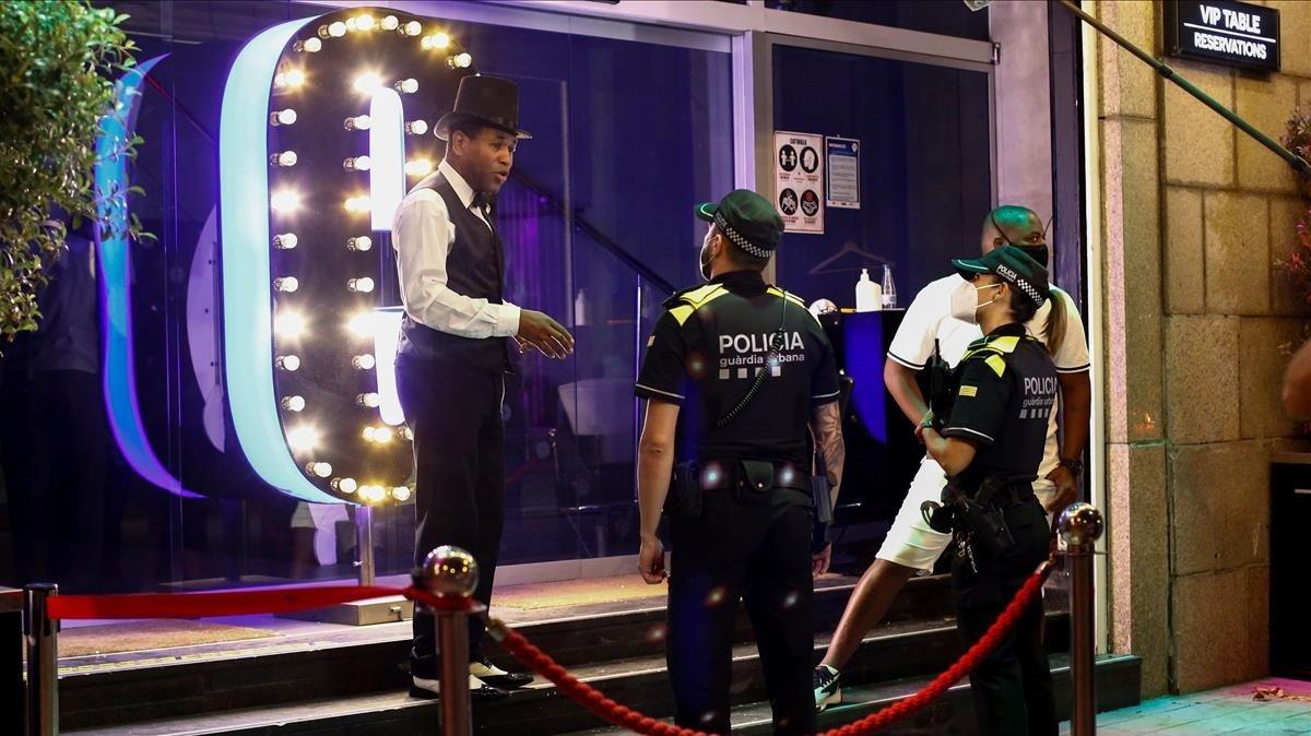 Una patrulla de la Guardia Urbana habla con un trabajador de un local de ocio nocturno de Barcelona el pasado día 26, tras el cierre de medianoche por el covid-19.