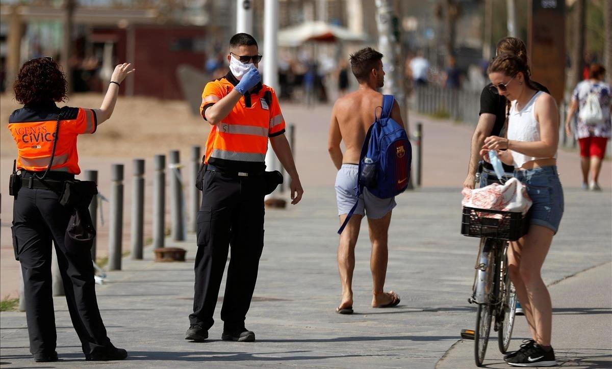 Unos agentes cívicos reclaman a una chica que se coloque la mascarilla, este sábado, en la Barceloneta.