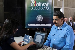Venezuela s President Nicolas Maduro participates in the process of buying a savings certificate in gold at Venezuela s Central Bank in Caracas.