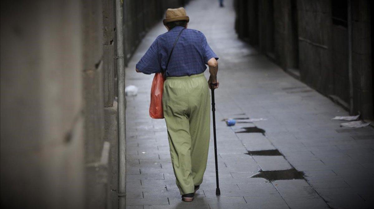 Unanciano pasea por una calle de Barcelona.