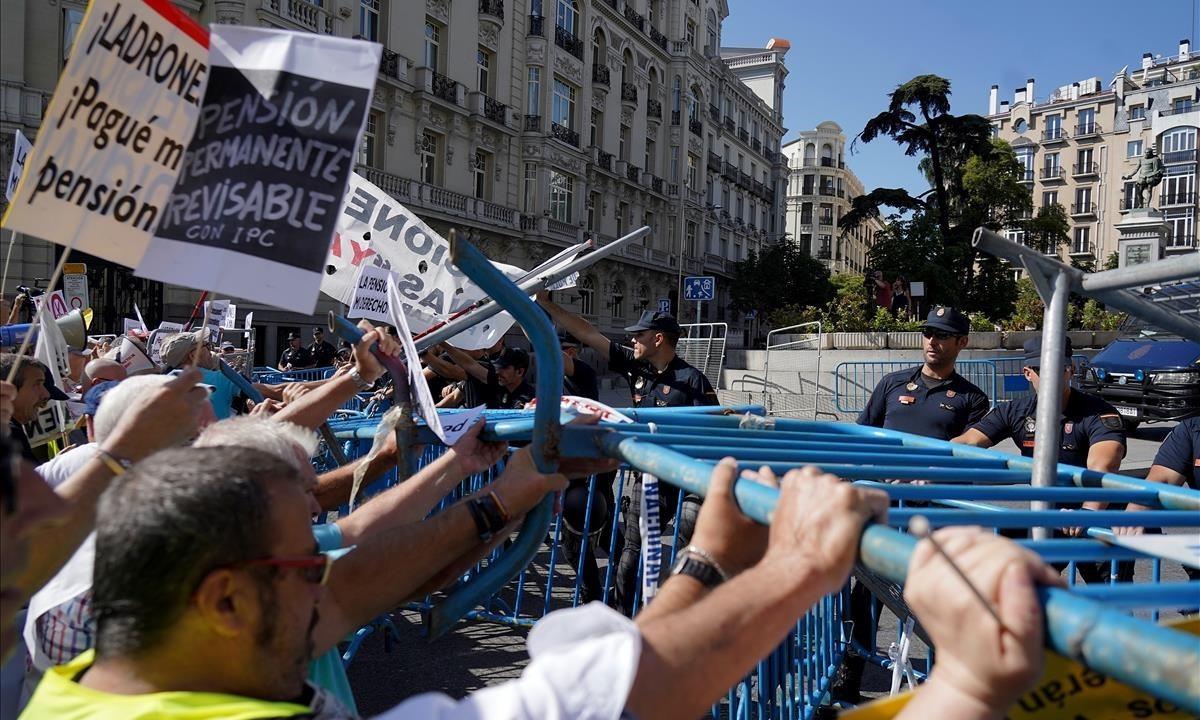 Efectivos de la Policía Nacional contienen la protesta de un grupo de pensionistas en las inmediaciones del Congreso de los Diputados.