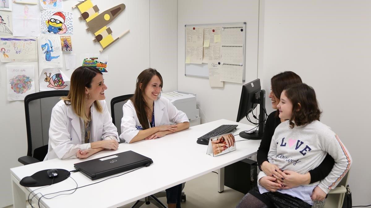 Las doctoras Gabriela Guillén (izquierda) y Raquel Hladun, con una madre y su hija paciente.