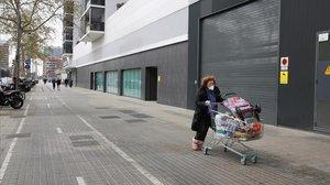Una mujer enmascarada empuja un carro con la compra por la Gran Via.