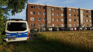 Un coche de policía se encuentra fuera de los edificios de apartamentos cercados y bajo cuarentena.