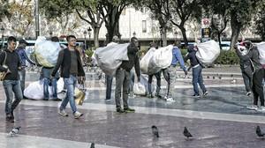 Un grupo de manteros en la plaza de Catalunya.