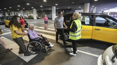 Un pasajero en silla de ruedas se sube a un taxi de servicios mínimos.